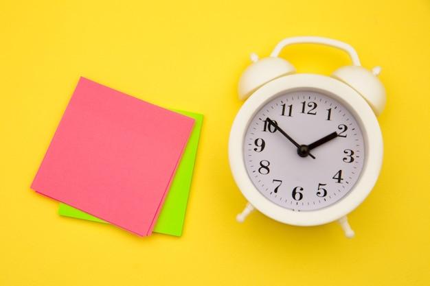 白い目覚まし時計と黄色のカラフルな付箋。