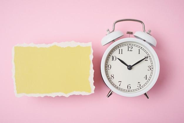 白い目覚まし時計とピンクの背景の空の破れた紙シート