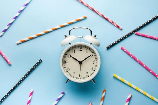 파란색 표면에 칵테일 멀티 종이 튜브 주위에 흰색 알람 시계. 위치.