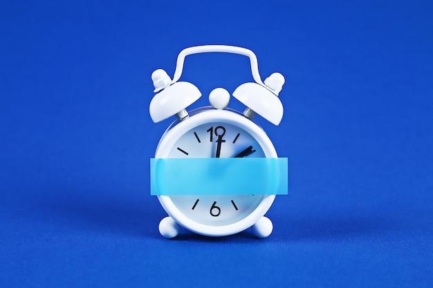White alarm clock blue. blank sticky note on clock. space copy. minimal concept.