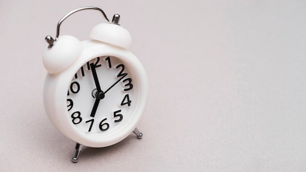 White alarm clock on colored background