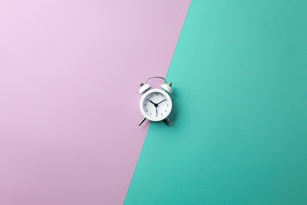 White alarm clock on colorful. concept in minimal style