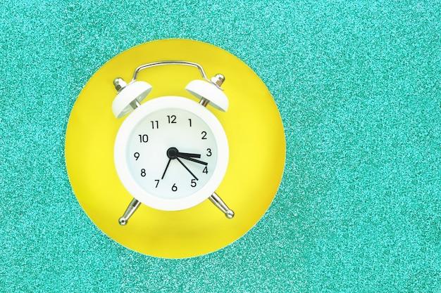 黄色の背景に光沢のある青緑色の段ボールの丸い穴に落ちる白い目覚まし時計。テキスト用のスペース。
