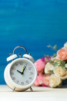 White alarm clock and flowers pink and red rose on wooden table and blue background