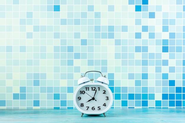 White alarm clock front a blue tile wall. copyspace