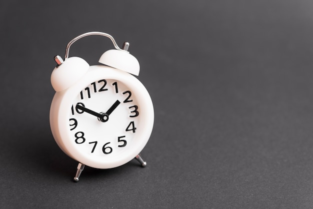 White alarm clock on gray background