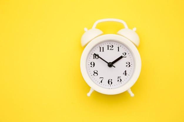 White alarm clock isolated on yellow trendy.