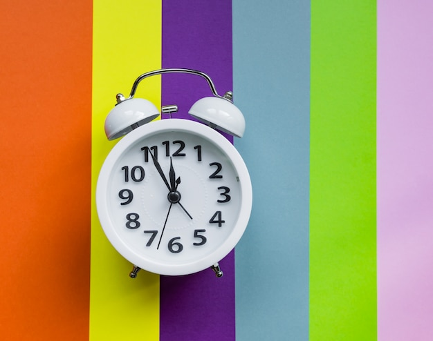 White alarm clock on multicolored striped background with copy space for text.