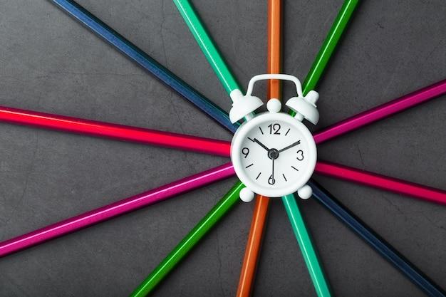 검정색 배경에 별 모양에 다른 색상의 연필에 흰색 알람 시계.