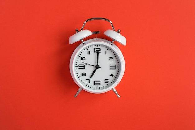 빨간색 배경에 흰색 알람 시계입니다. 평면도. 확대.