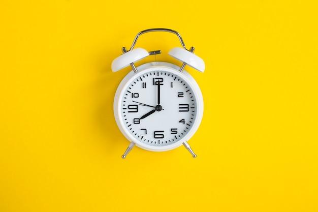 노란색 배경에 흰색 알람 시계입니다. 평면도. 확대.