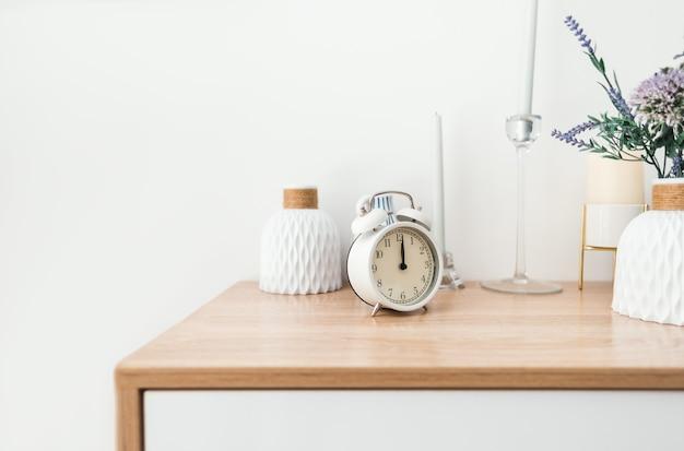 コピースペースと木製のテーブルの上の白い目覚まし時計。