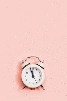 Белый будильник показывает около двенадцати часов с блестками, новогоднее рождественское понятие