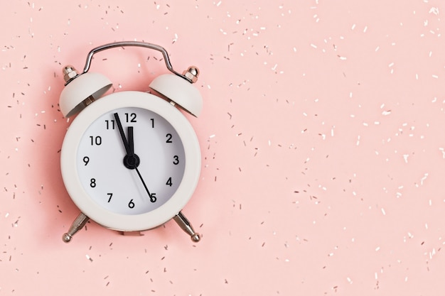White alarm clock shows about twelve oclock on pink paper covered with sequins