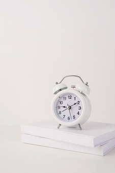 White alarm clock on stack of books mockup design