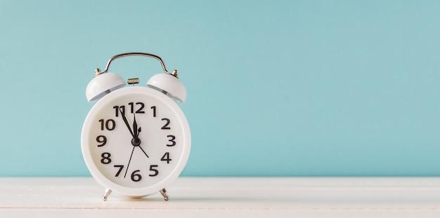 White alarm clock standing on wooden shelf on blue background.