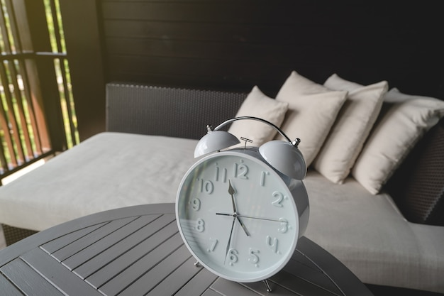 흰색 알람 시계는 침대 옆 탁자 위에 있습니다.