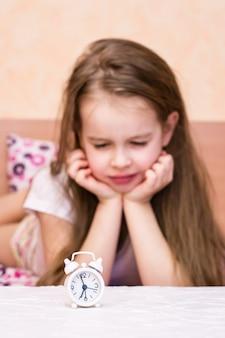 Белый будильник стоит на столе проснувшейся девушки