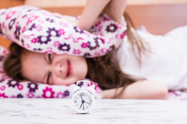 Белый будильник стоит на столе на фоне девушки, закрывающей уши подушками
