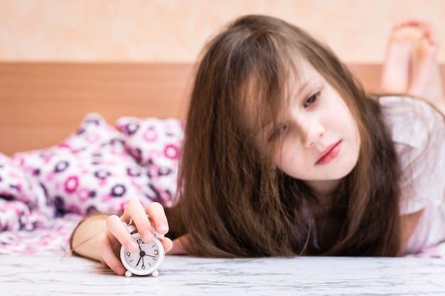Белый будильник стоит на столе на фоне просыпающейся девушки