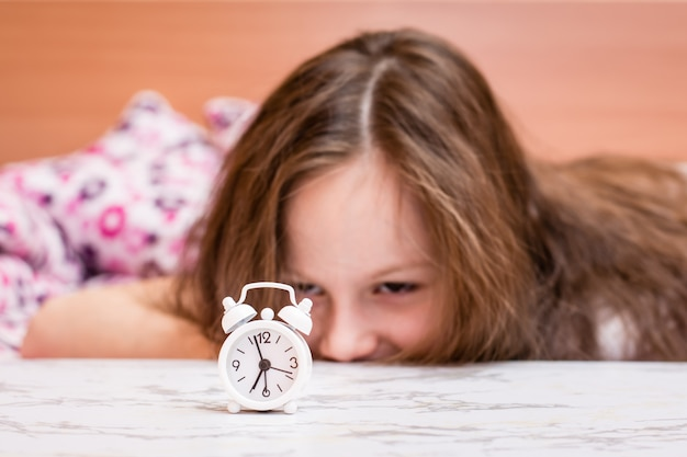 White alarm clock stands on the table of a waking up girl