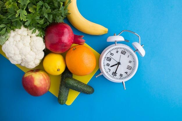 白い目覚まし時計、青の野菜や果物