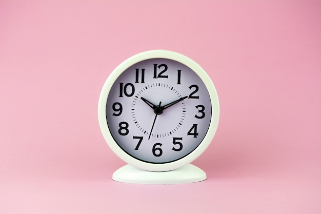 White alarm clock with big numbers on pink background.