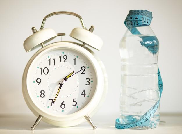 Белый будильник с бутылкой воды, синяя измерительная лента как концепция диеты - на белом фоне