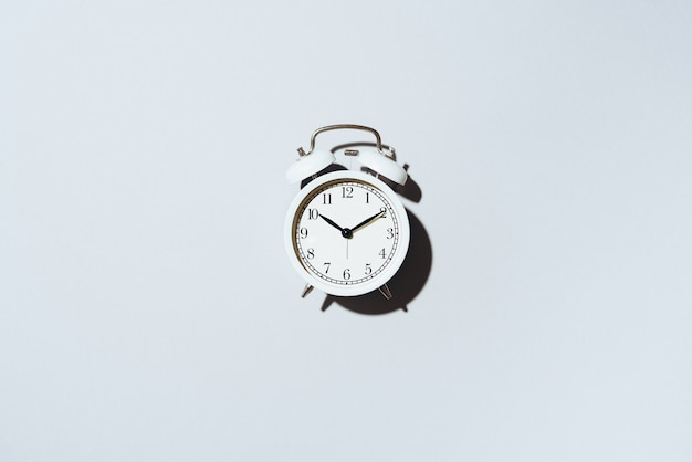 White alarm clock with hard shadow on grey background.