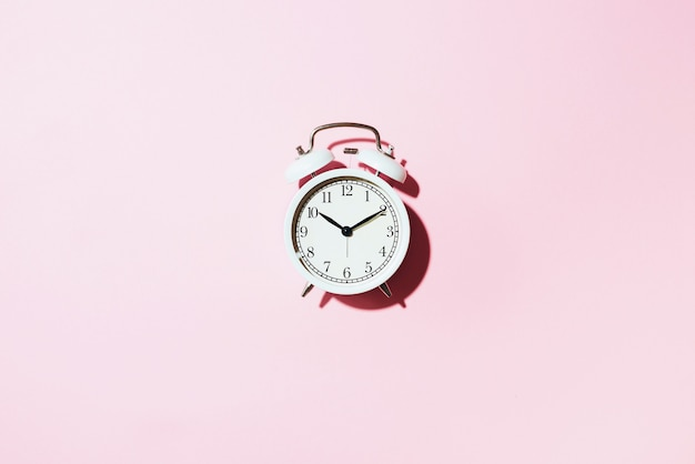 White alarm clock with hard shadow on pink background.