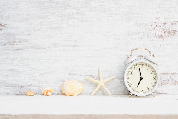 White alarm clock with starfish, sea shells on white rusty wood background. background concept for summer time holiday vacation, sea beach travel vacation time.