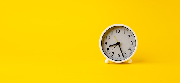 White alarm clock on yellow background with space for text, time ideas and work