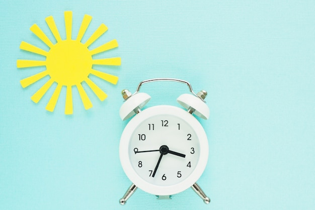 White alarm clock and yellow paper sun on a blue paper background. space for text.