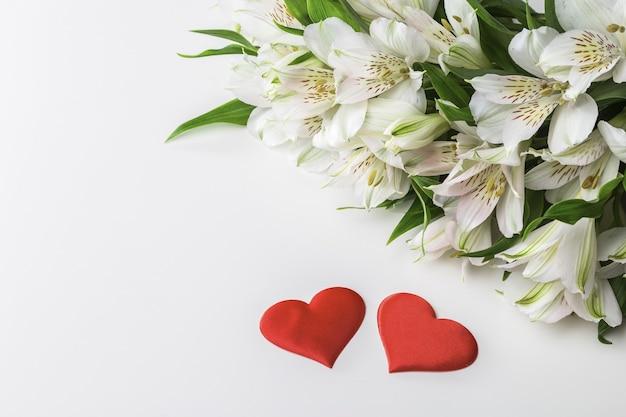 白いアルストロメリアの花束とコピースペースと白い背景の上の2つの赤いハート。バレンタインデーのポストカード。