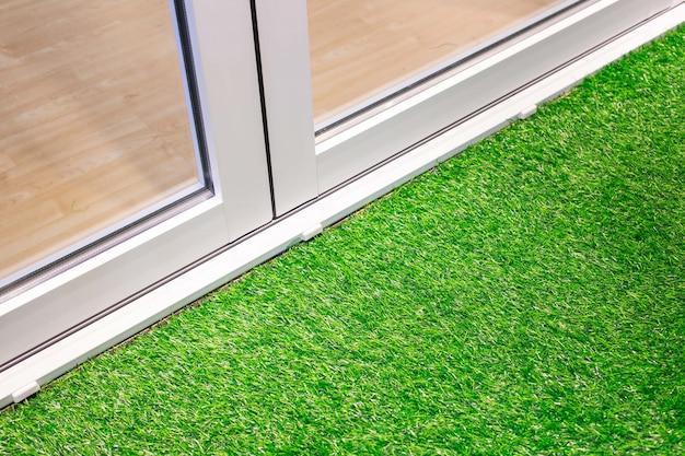 白いアルミのドアと草床の装飾