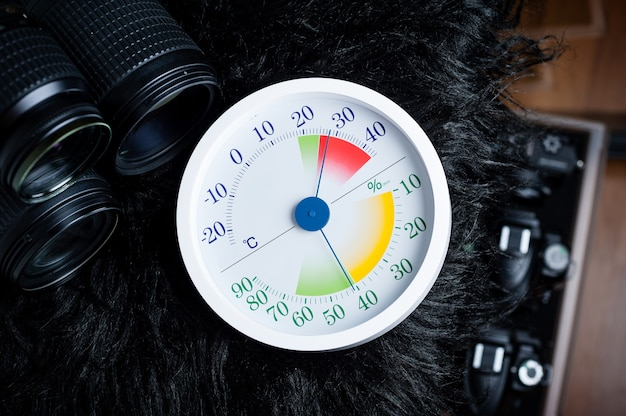 White analog thermometer and hygrometer with photography equipments