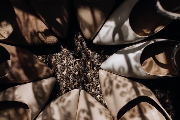 白とベージュの結婚式の靴の周りに囲まれ、真ん中に婚約指輪
