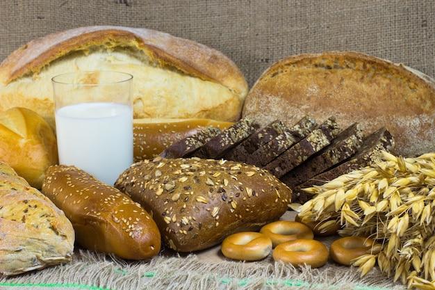 Белый и черный хлеб, багет, булочка, пучок овса, стакан молока на мешковине.