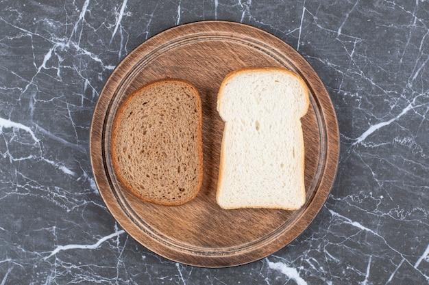 Белый и черный хлеб на доске, на мраморной поверхности