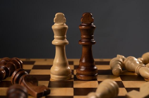 倒れた人物の間に立っている白と黒のチェスの王
