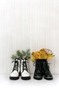 冬のモミの枝とコピースペースと白い木製の背景に黄色の紅葉と白と黒の女性の靴。