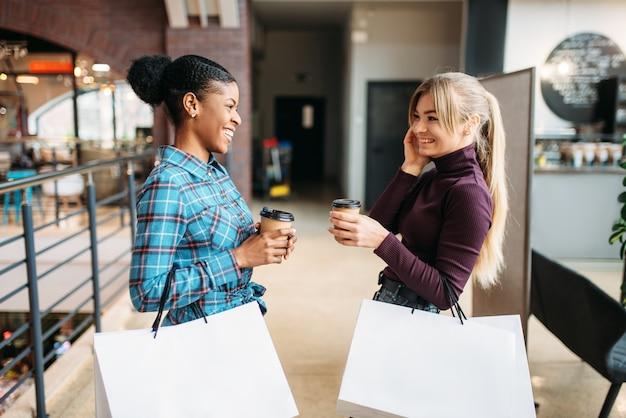 モールで買い物袋を持つ白と黒の女性