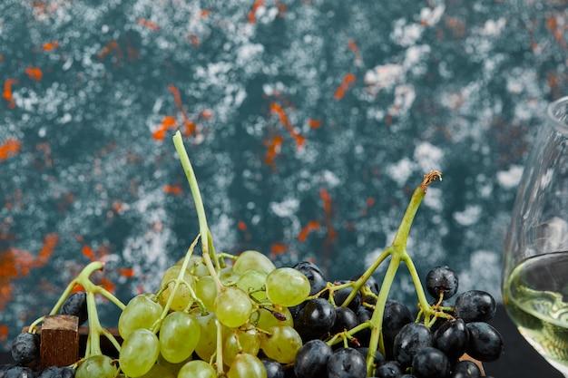파란색 배경에 와인 한 잔과 흰색과 검은 색 포도. 고품질 사진