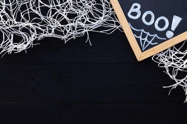 흰색과 검은색 할로윈 플랫레이. 검은 나무 배경에 분필 비문 boo와 거미줄. 복사 공간