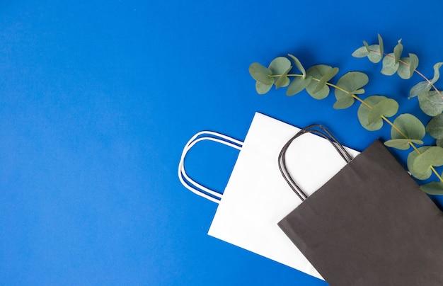 Белые и черные бумажные пакеты с ручками и листьями эвкалипта на синем фоне. плоский баннер, вид сверху, место для копирования, нулевые отходы, предметы без пластика. мокап эко-пакета