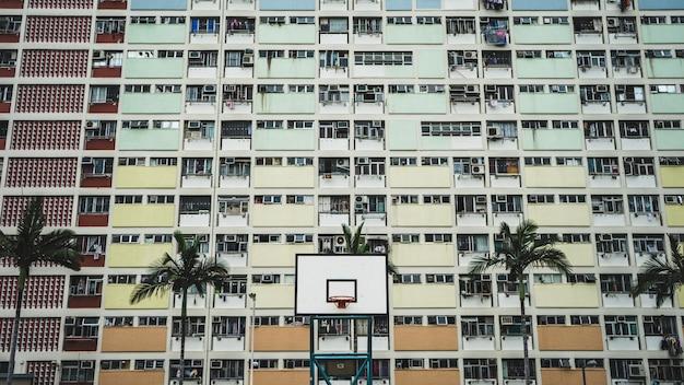 昼間の背の高い木々やコンクリートの建物の近くに白と黒のポータブルバスケットボールフープ