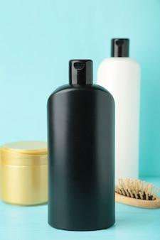 Белая и черная бутылка шампуня с расческой и маской для волос на синем. вид сверху