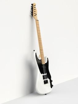 흰색 배경에 흰색과 검은색 6현 일렉트릭 기타, 벽에 기대어