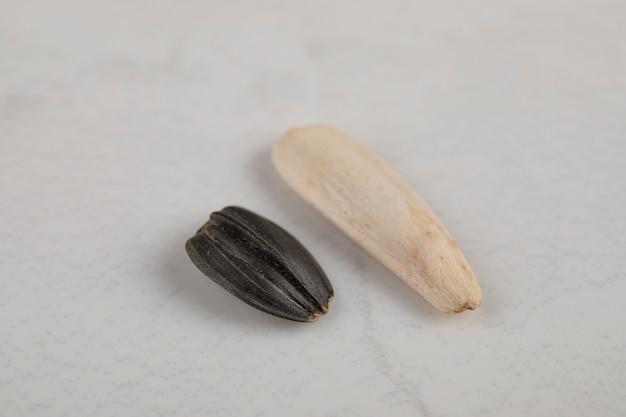 白い表面に置かれた白と黒のヒマワリの黒い種子