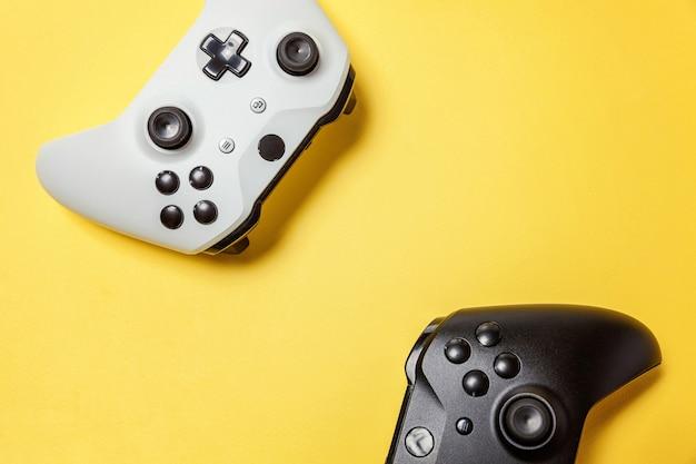 Белый и черный два джойстика геймпада, игровая консоль на желтом фоне